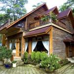 Ngôi biệt thự gỗ được bao bọc bởi cây xanh.